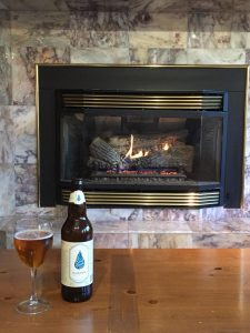 Good River Beer next to a fireplace.